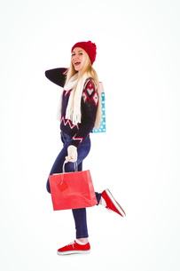 Festive blonde holding shopping bagsの写真素材 [FYI00004275]