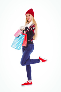 Festive blonde holding shopping bagsの写真素材 [FYI00004276]