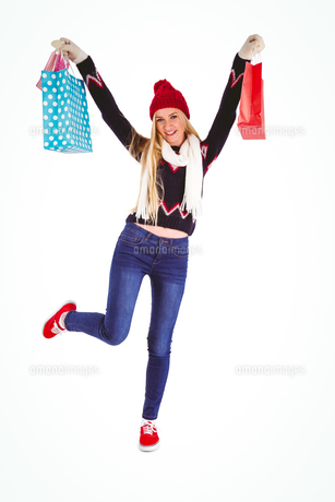 Festive blonde holding shopping bagsの写真素材 [FYI00004277]