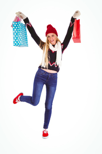Festive blonde holding shopping bagsの写真素材 [FYI00004277]