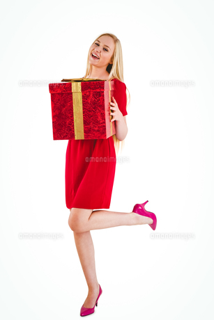 Pretty blonde in red dress holding giftの素材 [FYI00004291]