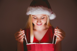 Festive blonde opening a gift bagの写真素材 [FYI00004296]