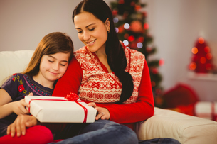 Festive mother and daughter holding christmas presentの写真素材 [FYI00004301]