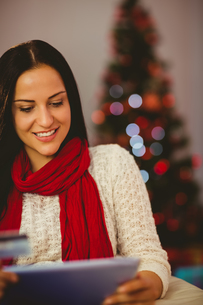 Pretty brunette shopping online with tablet at christmasの写真素材 [FYI00004303]