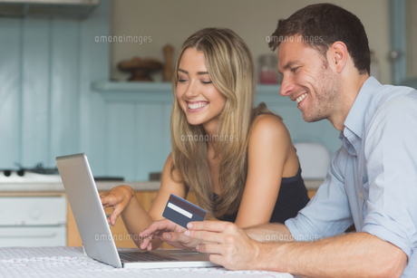 Cute couple using laptop together to shop onlineの写真素材 [FYI00004308]