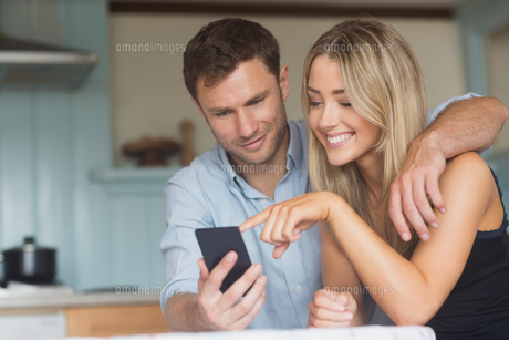 Cute couple using smartphone togetherの写真素材 [FYI00004309]