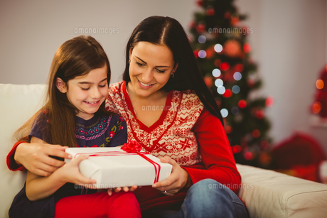 Festive mother and daughter holding christmas presentの写真素材 [FYI00004313]