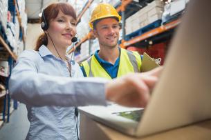 Smiling businesswoman wearing headset using laptopの写真素材 [FYI00004332]