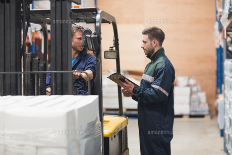 Warehouse worker talking with forklift driverの写真素材 [FYI00004338]