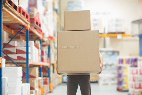 Worker carrying boxes in warehouseの写真素材 [FYI00004341]