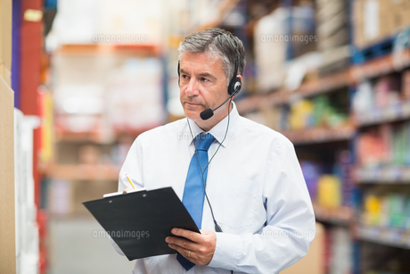 Warehouse manager wearing headset writing on clipboardの写真素材 [FYI00004344]