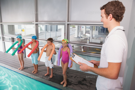 Swimming coach with his students poolsideの素材 [FYI00004353]