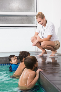 Cute kids in the swimming pool listening to coachの写真素材 [FYI00004361]