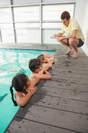 Cute swimming class listening to coachの写真素材 [FYI00004362]