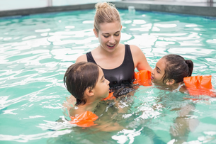 Cute swimming class in pool with coachの写真素材 [FYI00004365]