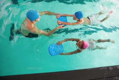 Cute swimming class in pool with coachの写真素材 [FYI00004366]