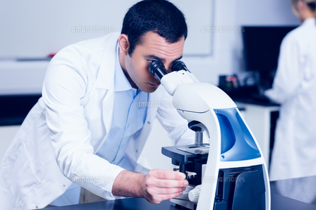 Science student looking through microscopeの写真素材 [FYI00004370]