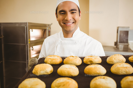 Baker smiling at camera holding tray of rollsの写真素材 [FYI00004383]