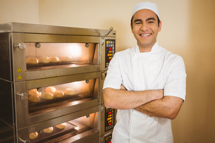 Baker smiling at camera beside ovenの写真素材 [FYI00004385]