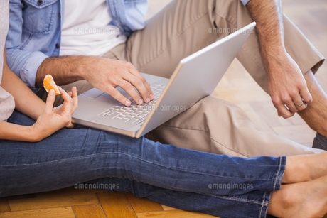 Mid section of couple sitting on floor using laptopの写真素材 [FYI00004388]