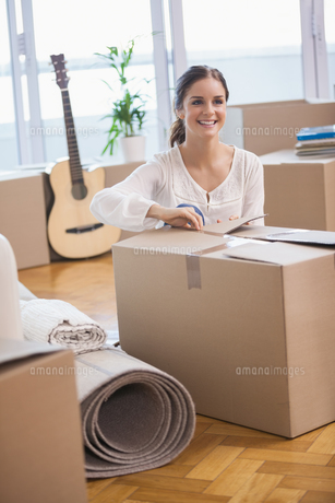 Smiling woman unpacking cardboard boxesの写真素材 [FYI00004389]