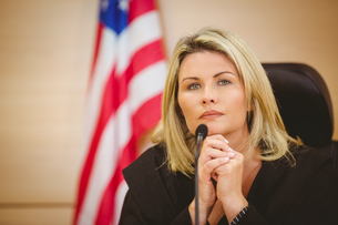 Portrait of a serious judge with american flag behind herの写真素材 [FYI00004406]