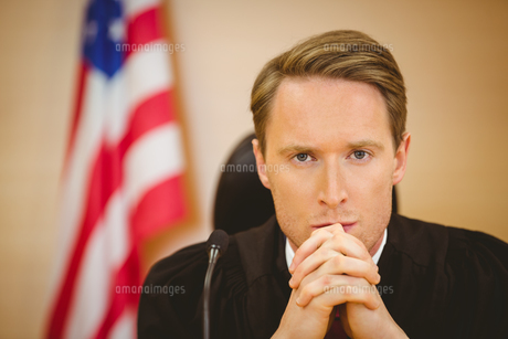 Portrait of a serious judge with american flag behind himの素材 [FYI00004409]