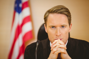 Portrait of a serious judge with american flag behind himの写真素材 [FYI00004409]