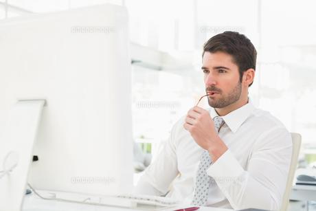 Serious businessman using computer monitorの写真素材 [FYI00004434]
