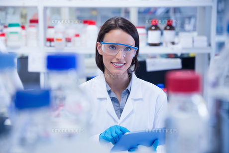 Smiling chemist wearing safety glasses and using tablet pcの写真素材 [FYI00004436]