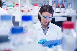 Chemist wearing safety glasses and using tablet pcの写真素材 [FYI00004437]
