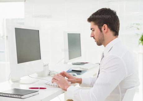 Classy businessman typing on keyboardの写真素材 [FYI00004438]