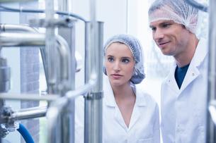 Smiling scientist with colleague looking metal gaugeの素材 [FYI00004439]