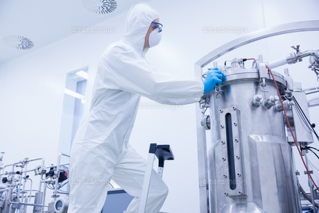 Scientist in protective suit standing on ladderの写真素材 [FYI00004440]