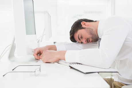 Tired businessman sleeping on keyboardの写真素材 [FYI00004443]