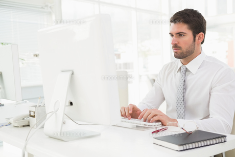 Concentrated businessman typing on keyboardの写真素材 [FYI00004445]