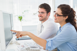 Smiling business coworkers pointing screen of computerの写真素材 [FYI00004451]