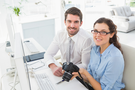 Smiling team holding digital cameraの素材 [FYI00004452]