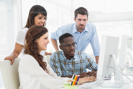 Concentrated coworkers using computer togetherの写真素材 [FYI00004476]