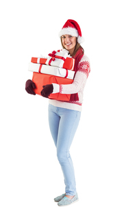 Festive brunette holding pile of giftsの写真素材 [FYI00004500]