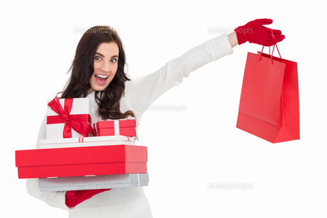 Excited brunette holding gifts and showing shopping bagの写真素材 [FYI00004510]