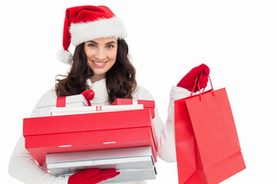 Festive brunette holding christmas gifts and shopping bagsの写真素材 [FYI00004511]
