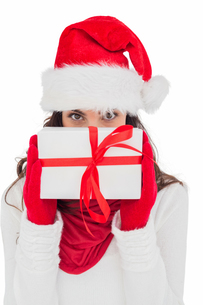 Brunette in red gloves and santa hat showing giftの写真素材 [FYI00004517]