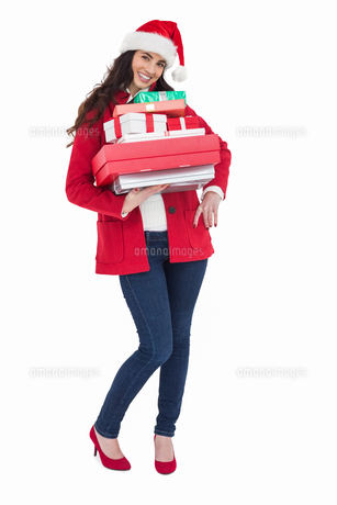 Festive brunette in santa hat and red coat holding pile of giftsの写真素材 [FYI00004518]