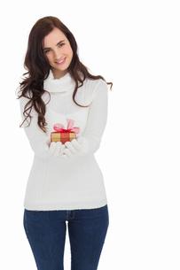 Smiling brunette in white gloves holding giftの写真素材 [FYI00004519]