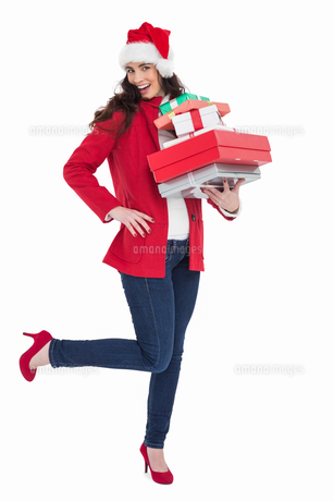 Excited brunette in red coat holding many giftsの写真素材 [FYI00004520]