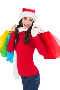 Festive brunette in winter wear holding shopping bagsの写真素材 [FYI00004521]