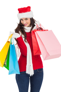 Smiling brunette in winter wear holding shopping bagsの写真素材 [FYI00004522]