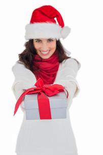 Festive brunette in santa hat giving giftの写真素材 [FYI00004523]