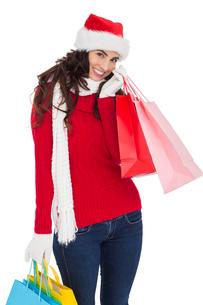 Happy brunette in winter wear holding shopping bagsの写真素材 [FYI00004524]